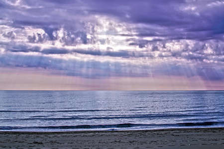 rays of sunshine filtering in the purple clouds, just after a storm on the sea Banque d'images - 95761247