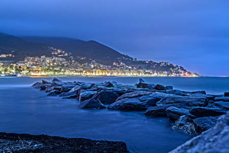 stormy evening on the seafront between the rocks of the Mediterranean Sea, in the Gulf of Varazze, Liguria, Italy Banque d'images - 96000143