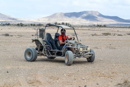 buggy racing on the sand road doing derapage at full speed amidst the desert of Fuerteventura, Canary Banque d'images - 95800835