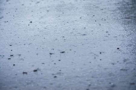 Grandes gouttes de pluie tombant sur la route asphaltée pendant une journée de pluie Banque d'images - 96000160