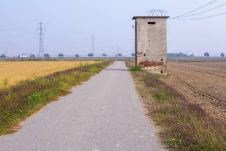 brick building along a small country road that crosses the rice fields just harvested, at the end of the summer, in Piedmont, Italy Banque d'images - 95761543