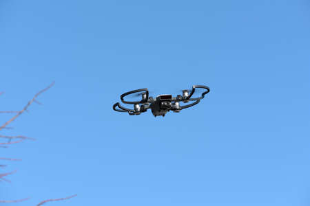 remote aerial quadcopter drone, with hight resolution camera, flying in the blue sky, which makes a survey of the territory, Italy Banque d'images - 96130509
