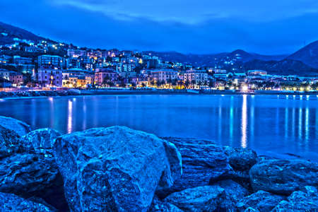 view from the sea of Varazze, a village of northern Italy, on the sea, during a beautiful summer evening, with the lights of the city's street lamps on the seafront Banque d'images
