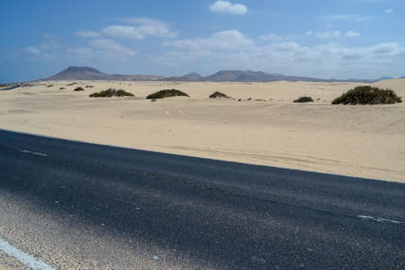 typical asphalted street in the desert, surrounded by white beach and dunes, Corralejo, Fuerteventura, Canary Islands, Spain