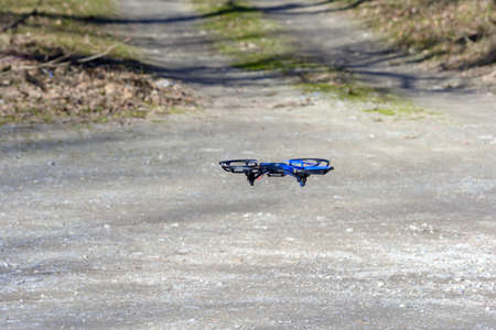 remote aerial quadcopter drone landing on dusty ground, with hight resolution camera, which makes a survey of the territory, Italy