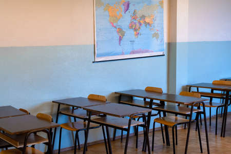 chairs and benches from which students follow the lesson, at school, with the geographical map hanging on the wall Banque d'images - 99409811