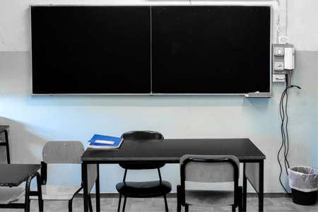 Classe de l & # 39 ; école avec un tableau suspendu sur le mur et le registre des heures sur le bureau Banque d'images - 99394405
