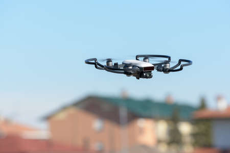 quadcopter drone in flight close to a town, which makes photographs with a high resolution camera, Italy