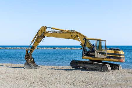 Excavatrice travaillant sur la plage à lisse le sable avant la saison d & # 39 ; été tôt Banque d'images - 99376755