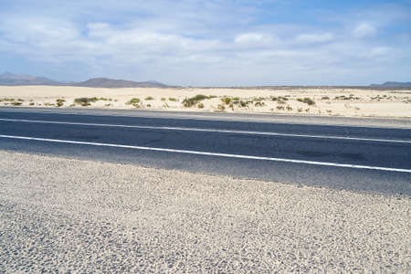 typical paved road drawn in the desert, surrounded by white beach, Corralejo, Fuerteventura, Canary Islands, Spain Banque d'images - 99396423