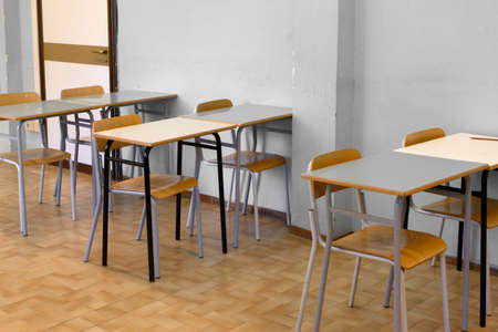 desks and chairs ready for the lesson, in a schoolroom, before the students arrive, in a middle school Banque d'images