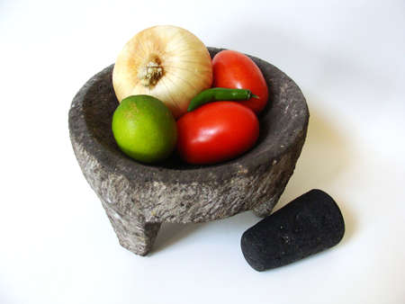 A grinding stone and ingredients for Mexican cooking