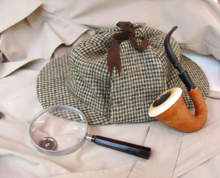 sherlock: Tweed hat, calabash pipe, magnifying glass and trench coat Stock Photo