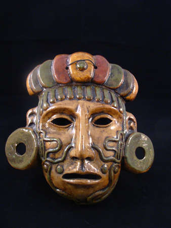 Clay mask of a Maya warrior with tattoos and ear spools photo