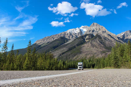 low perspective: white truck driving through canadian rocky mountains during summer, taken from a low perspective with blue sky and green trees