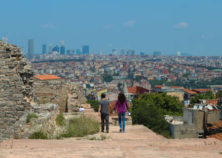 teenaged boy: teenaged girl and boy walking hand in hand in the city on old city wall