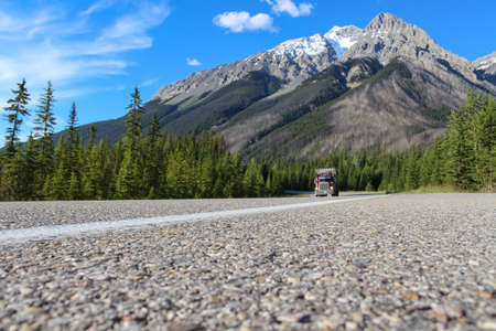 low perspective: ruby truck driving through canadian rocky mountains during summer, taken from a low perspective with blue sky and green trees