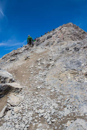 scrambling: looking up ha ling mountain in canada with lots of people on it and blue sky Stock Photo
