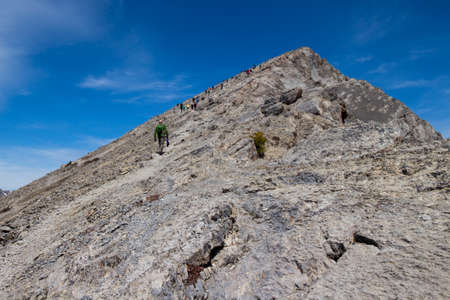 ling: looking up ha ling mountain in canada with lots of people on it and blue sky Stock Photo