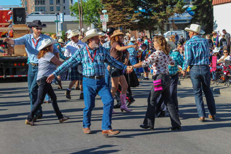 calgary stampede: people on the street doing the traditional square dance during calgary stampede parade