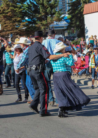 calgary stampede: a policeman and an older lady on the street doing the traditional square dance during calgary stampede parade