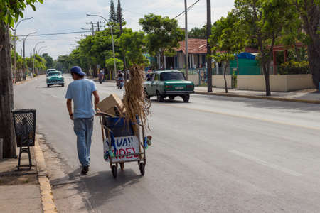recolector de basura: colector carbage caminando con su carro de mano por una calle de Cuba, mirando a un cubo de basura