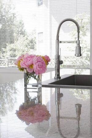 granite kitchen: vase of pink peonies and chartreuse chrysanthemums on sink of modern kitchen - reflection in granite countertop