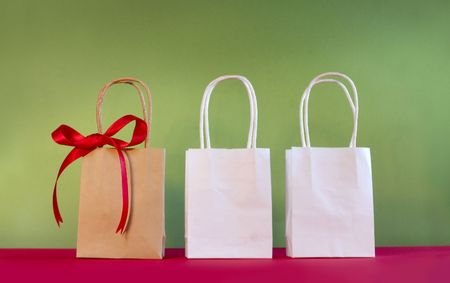 three shopping bags decorated with bow on red and green christmas background