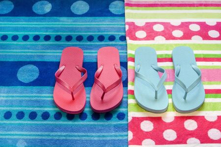 pink and blue flop flops on contrasting towels for the summertime