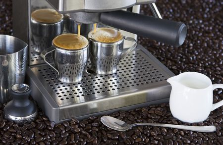 espresso machine dispenses shots of fresh coffee with beans, spoon in background Stock Photo