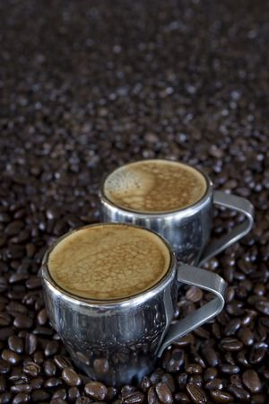 two shots of fresh espressso coffee in stainless steel cups with beans in background Stock Photo