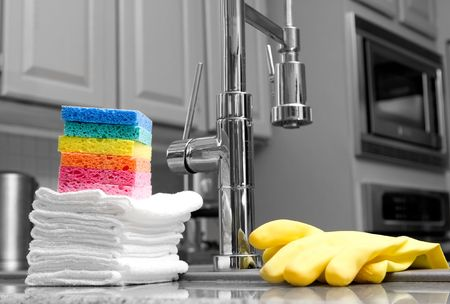 colorful sponges, cloths, and yellow gloves in modern kitchen - housework