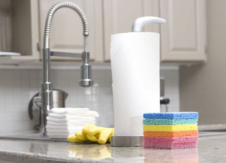 rainbow sponges, paper towels, gloves in modern kitchen for housework