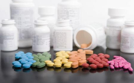 and vitamin: rainbow of prescriptions drugs with white bottles on black Stock Photo