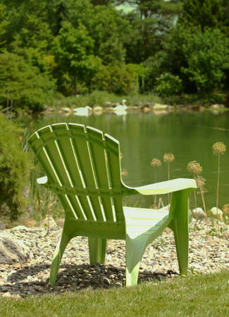 plastic adirondack style chair by a pond in the summer sun