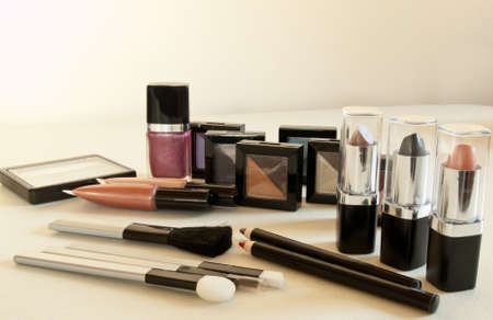 assortment of womens cosmetics on off-white background