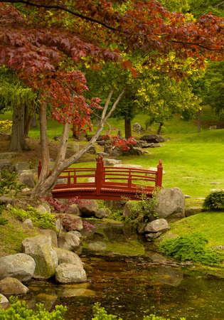 red foot-bridge in a beautiful garden in autumn