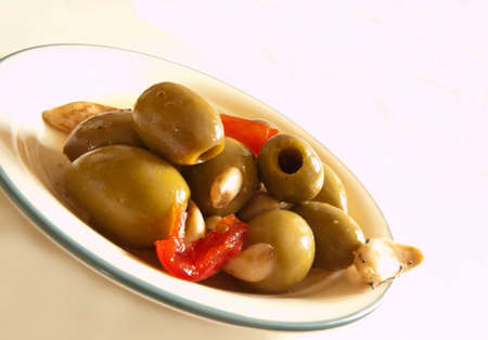cloves of garlic stuffed into green olives on a plate Stock Photo