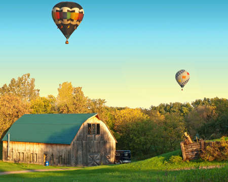 barn with hot air balloons drifting above Stock Photo - 17526769