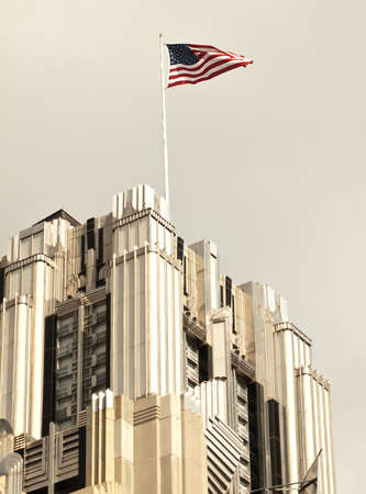 american flag flying atop a skyscraper Editorial