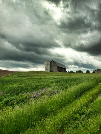 barn and farmland with stormy sky