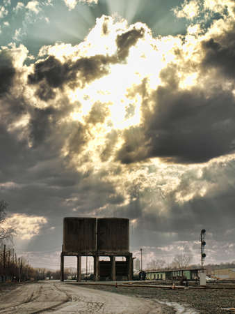urban railyard with clouds and sunrays Stock Photo