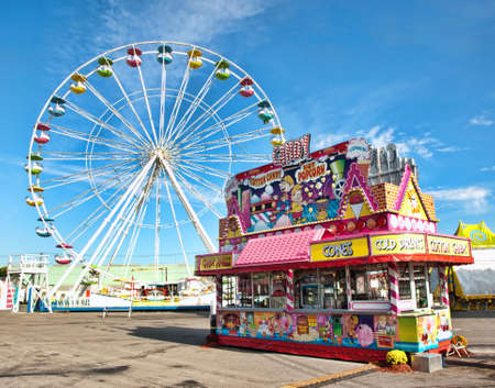 fairs: ferris wheel and candy stand on a midway at a fair