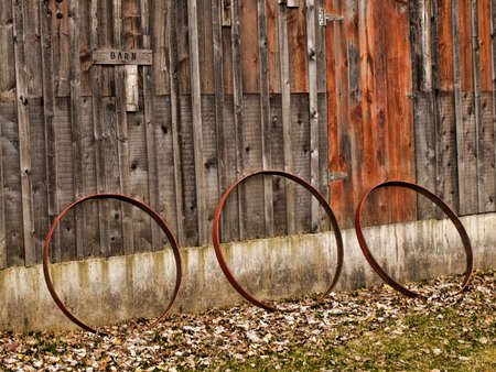 rusting: rusting cast iron wagon wheels leaning against barn wall Stock Photo