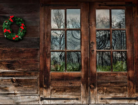 christmas cabin: doors of a rustic wood cabin with christmas wreath  Stock Photo