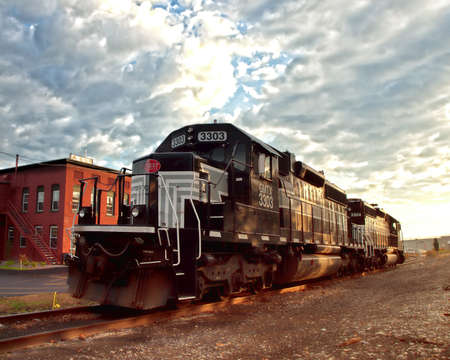 Solvay, New York, USA. October, 22,2015. The Fingerlakes Railway locomotive parked on the railway tracks in front of Chinatown Furniture Store, in early morning