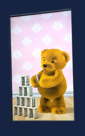 Rochester, New York, USA. October 24, 2015. Strong National Museum of Play. Digital picture of a Teddy Bear playing with Dominos Editorial