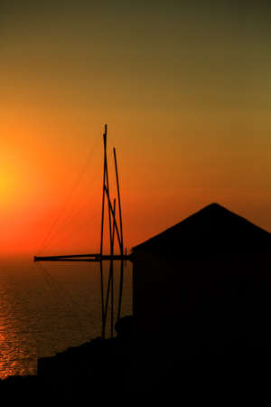 Greek windmill silhouetted against the sunset Oia Santorini photo