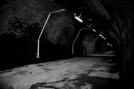 Long tunnel of an old railway viaduct taken in black and white photo