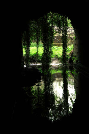 abbey: The reflection of water and an archway from inside the arch underground Stock Photo